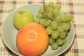 Fresh Green Grapes, Apple And Grapefruit On A Table