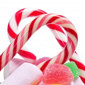 closeup of some candy canes and other candies on a white background