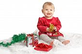 Smiling Baby Girl In Red Velvet Dress Sits With Holiday Gifts
