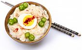 American Korean Style Dukjuk Chicken Porridge with peppers, boiled egg and chili powder.