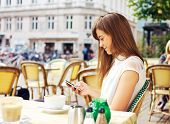 picture of cosmopolitan  - Attractive woman in a street cafe reading a text message from her phone - JPG