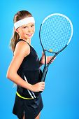 Portrait of a girl tennis player holding tennis racket. Studio shot.