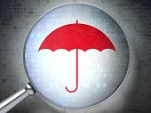 Magnifying optical glass with Umbrella icon on digital backgroun