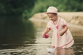 little girl plays with paper boats