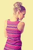foto of mini dress  - portrait of a young beautiful woman with blond hair in a bun wearing tight bright pink mini dress on fit slim body with retro effect - JPG