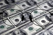 Closeup of several hundred dollar bills isolated on white background with glasses to bring money into focus