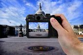 Hand holding camera taking photograph of US Capitol building by tourise