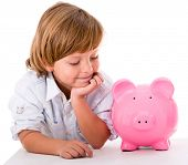 Happy boy with savings in a piggybank - isolated over a white background