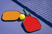 Pickleball - Two Paddles and A Ball With Net Shadow