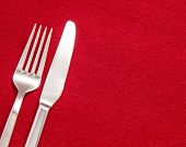 stock photo of banquet  - Silver Fork and knife on red table cloth - JPG