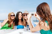 summer holidays and vacation - girls taking photo with digital camera in cafe on the beach