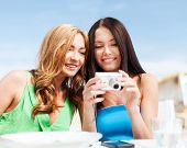summer holidays, vacation and technology - girls looking at digital camera in cafe on the beach