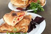 Pizza calzone on plates on wooden table