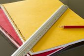closed notebooks with pencil and slat
