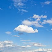 stock photo of stratus  - fluffy cumulus cloud in blue sky under stratus clouds - JPG