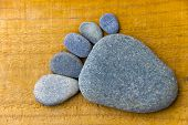 pic of flat-foot  - A foot made of pebbles on wooden background - JPG