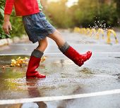 stock photo of rainy weather  - Child wearing red rain boots jumping into a puddle - JPG