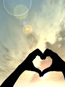 Concept or conceptual heart shape or symbol made of human or woman and man hand silhouette over a sky at sunset vertical background