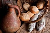stock photo of communion  - Wine loaves of bread and fresh fish in an old basket - JPG