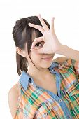 Casual young asian woman doing the ok sign on eye. Isolated on the white background.