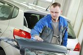 repairman worker in automotive industry wiping car body painting or repaint at auto repair shop