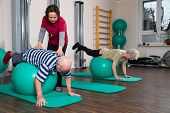 a physiotherapist trained with two pensioners with gymnastic balls