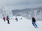 MONT-TREMBLANT, QUEBEC, CANADA -FEBRUARY 9: Skiers and snowboarders are sliding down an easy slope a