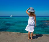 Girl rear view in Formentera Ibiza beach turquoise Mediterranean sea background