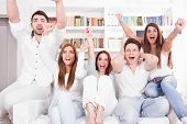 stock photo of indoor games  - excited cheerful friends watching football game on tv - JPG