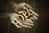 stock photo of word charity  - Closeup of male hands holding a word of HOPE