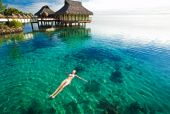 picture of beach hut  - Young woman in white bikini swimming in a coral lagoon - JPG