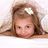 Closeup portrait of cute little girl with flower in hair lying down in the bed, covered with soft bl