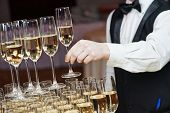 stock photo of over counter  - Waiter hand with glass of champagne over pyramid during catering at party - JPG