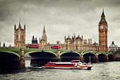 London, the UK. Big Ben, the Palace of Westminster and the River Thames. Red buses, red boat, the ic