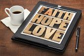 faith, hope and love - a collage of words in vintage letterpress wood type on a digital tablet with a cup of coffee