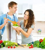 Young Man Cooking. Happy Couple on a Kitchen at Home Eating Fresh Vegetable Salad. Diet. Dieting. Lo