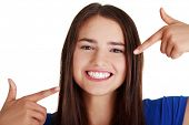 Teen girl pointing on her perfect teeth, isolated on white