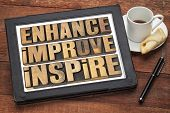 enhance, improve, inspire - a collage of motivational word in vintage letterpress wood type on a dig
