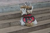 Colorful theatrical mask of mummer sitting