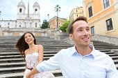 Romantic travel couple on Spanish Steps, Rome, Italy holding hands in love. Young interracial couple walking on the travel landmark tourist attraction icon during their romance Europe holiday vacation