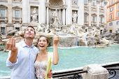 Travel couple trowing coin at Trevi Fountain, Rome, Italy for good luck. Happy young couple smiling