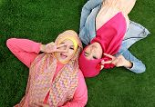 image of muslimah  - Portrait of close up two beautiful happy muslim woman lying on grass - JPG