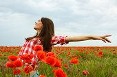 Young beautiful woman walking and dancing through a poppy field, summer outdoor.