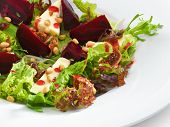 Fresh vegetarian gourmet salad with baked beetroot and cheese served on a white round plate. Isolate
