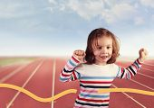 portrait of a girl runner running towards a finish line