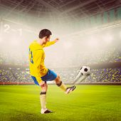 soccer or football player is kicking ball on stadium, warm colors toned