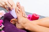 stock photo of stimulation  - Woman having a pedicure treatment at a spa or beauty salon with the pedicurist massaging the soles of her feet with a pumice stone to cleanse dead skin and stimulate the tissue - JPG