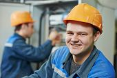 image of electrician  - Happy young adult electrician builder engineer in front of his co - JPG