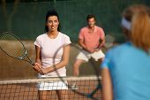 Young people playing tennis, mixed doubles, smiling.