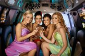 stock photo of limousine  - Group of beautiful elegant smiling girls celebrating in limousine - JPG